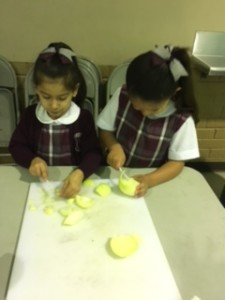 The girls are cutting an onion and realize that it causes tears.